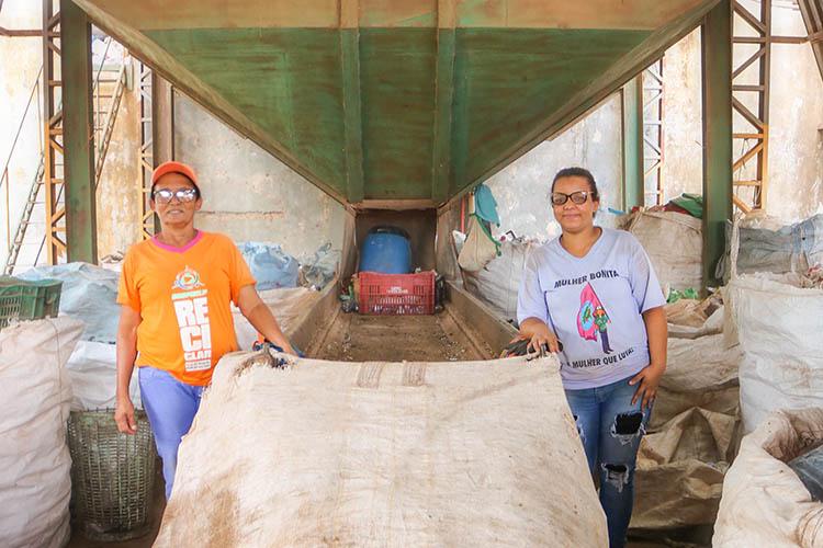 A foto mostra Miriam Silva Benvindo, cooperada da Cooprelp, e Catarina de Fátima Vaz, presidente da cooperativa de reciclagem, segurando um saco utilizado para a coleta de materiais recicláveis,