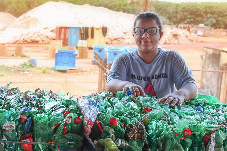 A foto mostra Miriam Silva Benvindo, cooperada da Cooprelp, apoiada em garrafas plásticas que serão destinadas à reciclagem.